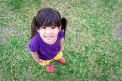 在绿草的逗人喜爱的亚洲孩子微笑 库存照片