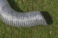 在绿草的铝透气管子为临时使用我 库存图片
