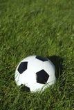 在绿草的经典黑白足球橄榄球 免版税图库摄影