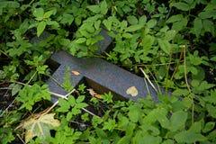 在绿草的黑石基督徒十字架的照片 库存照片