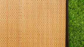 在绿草纹理背景的亚洲被编织的木头或藤条席子 免版税库存图片