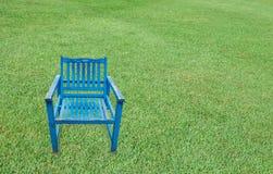 在绿草背景的古色古香的蓝色木椅子 免版税库存图片