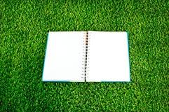 在绿草背景的笔记本 免版税库存图片