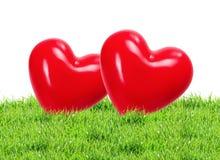 在绿草背景的红色心脏 免版税图库摄影