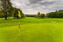在绿草背景的红色高尔夫球旗子 免版税图库摄影