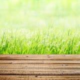 在绿草背景的老木桌 免版税库存图片