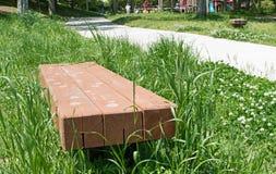 在绿草领域的长凳在公园 免版税库存图片