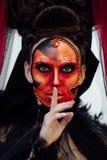 在黑葡萄酒礼服的巫婆画象 有红色艺术的妇女寡妇补偿万圣夜 库存照片