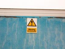 在说蓝色的墙壁上的一个标志警告反攀登油漆 免版税库存照片