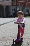 在滑行车的微笑的正面小女孩骑马在城市 免版税图库摄影