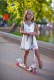 在滑行车的美丽的小孩girlin礼服在a 库存照片