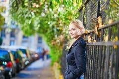 在巴黎街道上的少妇在一个晴朗的秋天或春日 免版税库存照片