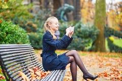 在巴黎街道上的美丽的少妇在一晴朗的秋天天 免版税库存照片