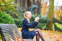 在巴黎街道上的美丽的少妇在一晴朗的秋天天 图库摄影
