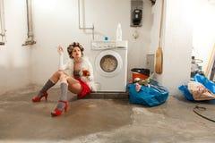 在洗衣店不耐烦的主妇 免版税库存图片