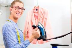 在洗衣店商店电烙的夹克的擦净剂 库存图片