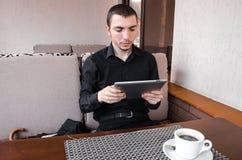 在黑衣服用途数字式片剂的愉快的商人在咖啡在咖啡馆的 库存照片