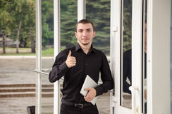 在黑衣服的愉快的商人与数字式片剂在办公室做一个姿态赞许 图库摄影