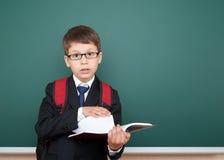 在黑衣服的男生画象在与红色背包和书,教育概念的绿色黑板背景 免版税库存照片