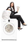 在洗衣机的女实业家洗涤的金钱 免版税库存图片