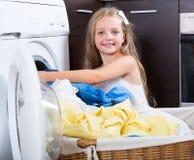 在洗衣机附近的逗人喜爱的小女孩 免版税图库摄影
