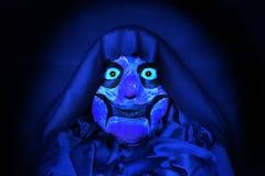 在黑衣裳的可怕面具在蓝色背景 图库摄影