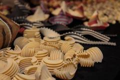 在黑表上的未煮过的被统治的和弯曲的意大利面团 库存图片
