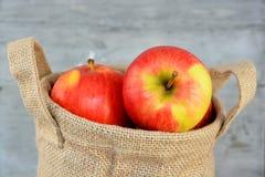 在黄麻袋子的有机苹果 库存照片