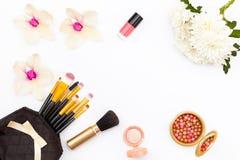 在黑袋子的构成刷子、花、兰花和菊花、指甲油和其他化妆用品在白色背景 库存照片