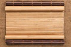 以在麻袋布的一个原稿的形式两竹子席子扭转了 库存图片