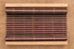 以在麻袋布的一个原稿的形式两竹子席子扭转了 免版税库存照片