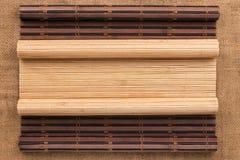 以在麻袋布的一个原稿的形式两竹子席子扭转了 图库摄影