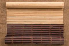 以在麻袋布的一个原稿的形式两竹子席子扭转了 免版税库存图片