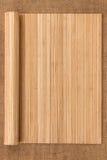 以在麻袋布的一个原稿的形式竹席子扭转了 免版税库存图片