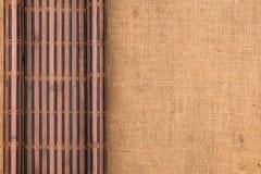 以在麻袋布的一个原稿的形式竹席子扭转了 免版税图库摄影