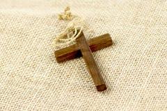 在麻袋布的木十字架 库存图片