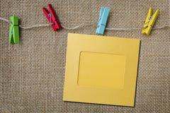 在麻袋布背景的五颜六色的纸照片框架 库存图片