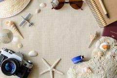 在麻袋布背景的旅行和假期辅助部件 库存图片