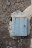 在破裂的墙壁上的蓝色邮箱 免版税库存图片