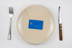 在破裂的板材上是塑料信用卡、下把谎言叉子和刀子,白色背景,顶视图 库存照片