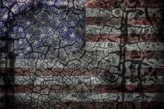 在破裂的水泥墙壁上的退色的美国国旗 图库摄影