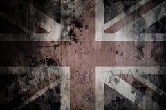 在破裂的水泥墙壁上的退色的英国旗子 免版税库存图片