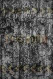 在破裂的水泥墙壁上的退色的道路危险标志 免版税库存照片