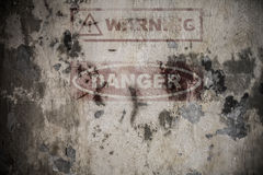 在破裂的水泥墙壁上的退色的道路危险标志 图库摄影