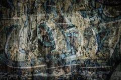 在破裂的水泥墙壁上的退色的Grafiti 免版税库存图片
