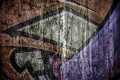 在破裂的水泥墙壁上的退色的Grafiti 库存图片