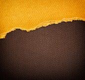 在黑褐色帆布背景的葡萄酒黄色被撕毁的纸 库存照片