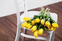 在说谎在古色古香的白色椅子的静物画的美丽的明亮的黄色郁金香 免版税库存图片