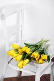 在说谎在古色古香的白色椅子的静物画的美丽的明亮的黄色郁金香 库存照片