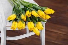 在说谎在古色古香的白色椅子的静物画的美丽的明亮的黄色郁金香 图库摄影